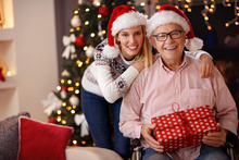 senior man and caregiver wearing santa hats.