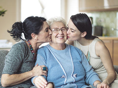Two younger women kissing an older woman on the cheek